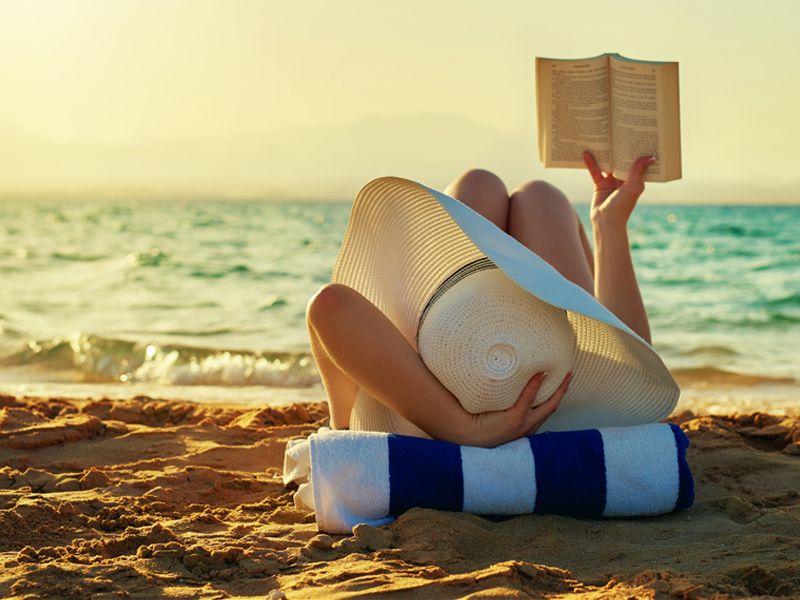 donna sdraiata sulla sabbia dorata spiaggia cappello di paglia telo spugna bianco blu tiene in mano romanzo ora lettura mare Quale libro leggere sotto l'ombrellone? 10 libri per l'estate 2018