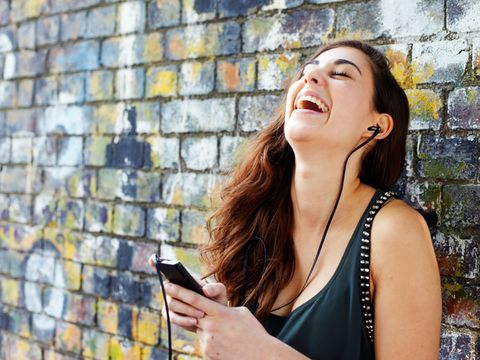 Mobile phone, Jewellery, Happy, Wall, Sleeveless shirt, Brick, Fashion accessory, Beauty, Street fashion, Tooth,