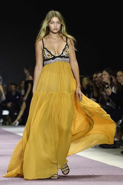 Yellow, Hairstyle, Shoulder, Fashion show, Joint, Runway, Waist, Fashion model, Style, Formal wear,