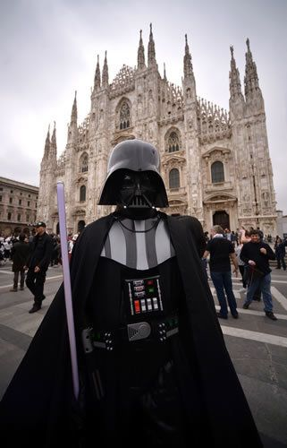 Darth vader, Supervillain, Standing, Cloak, Fictional character, Spire, Costume, Pedestrian, Cape, Costume accessory,