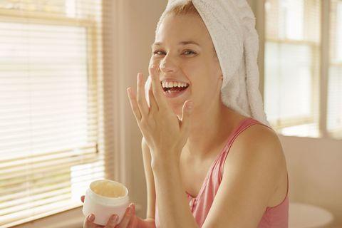 Ragazza si applica la crema viso in bagno