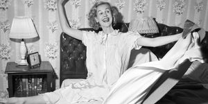1950s SMILING HAPPY GLEEFUL WOMAN WAKING UP GETTING OUT OF BED FLINGING BACK SHEETS AND BLANKETS