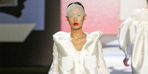 <p>The show opened with a sheer shirt dress striped with pieces of blue silk and adorned with extravagant, puffed sleeves ringed with oversized cuffs. And the closing white number was as show-stopping as you could hope for, layers of panniered shirt tails