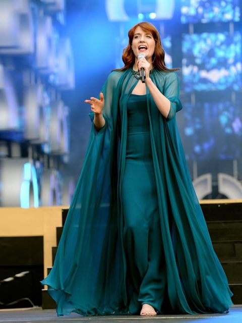 <p>Florence Welch in a deep turquoise silk crepe strapless evening gown with a matching silk chiffon cape featuring a crystal broach closure at the neck.</p>