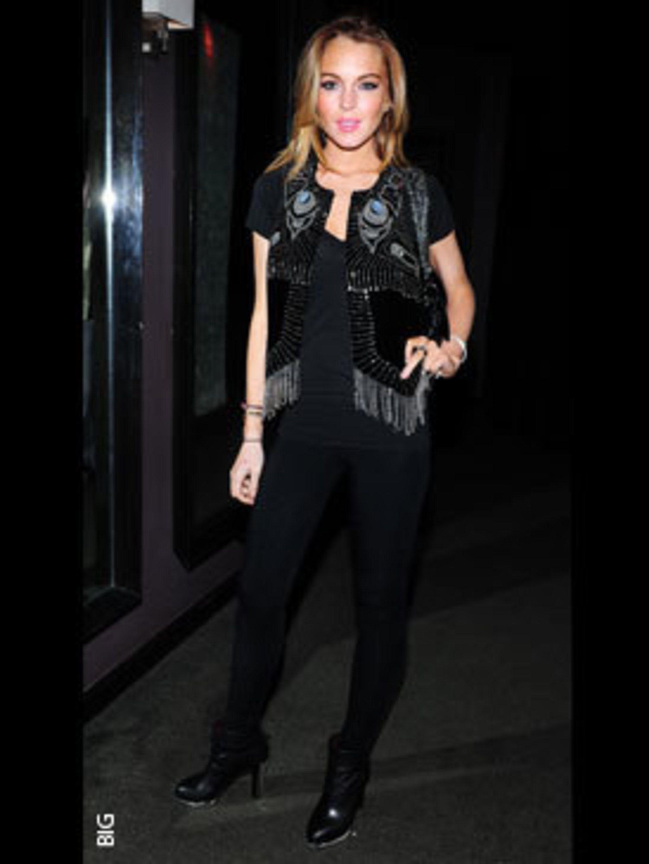 <p>Lindsay Lohan in Chloe boots, Ray-Ban sunglasses, and Mayle bag.</p>