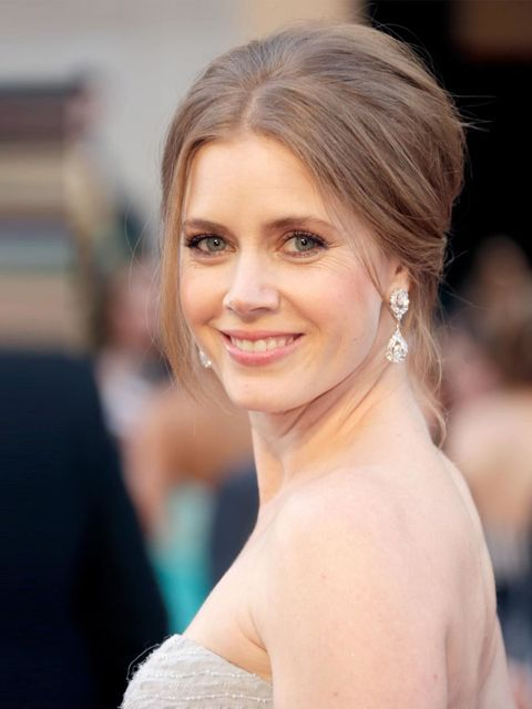 <p>Amy Adams Oscars look is polished and fresh faced. She's gone ever so slightly bridal with a beyond beautiful Oscar De La Renta dress complimented by a simple wispy up do and glowing contoured cheeks. It's safe but perfectly photogenic, which is all th