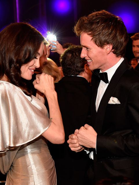 """<p>Eddie… flexing his guns with <a href=""""http://www.elleuk.com/now-trending/woman-of-the-week-angelina-jolie-humanitarian-work-honorary-dame"""">Angelina Jolie</a>.</p>"""