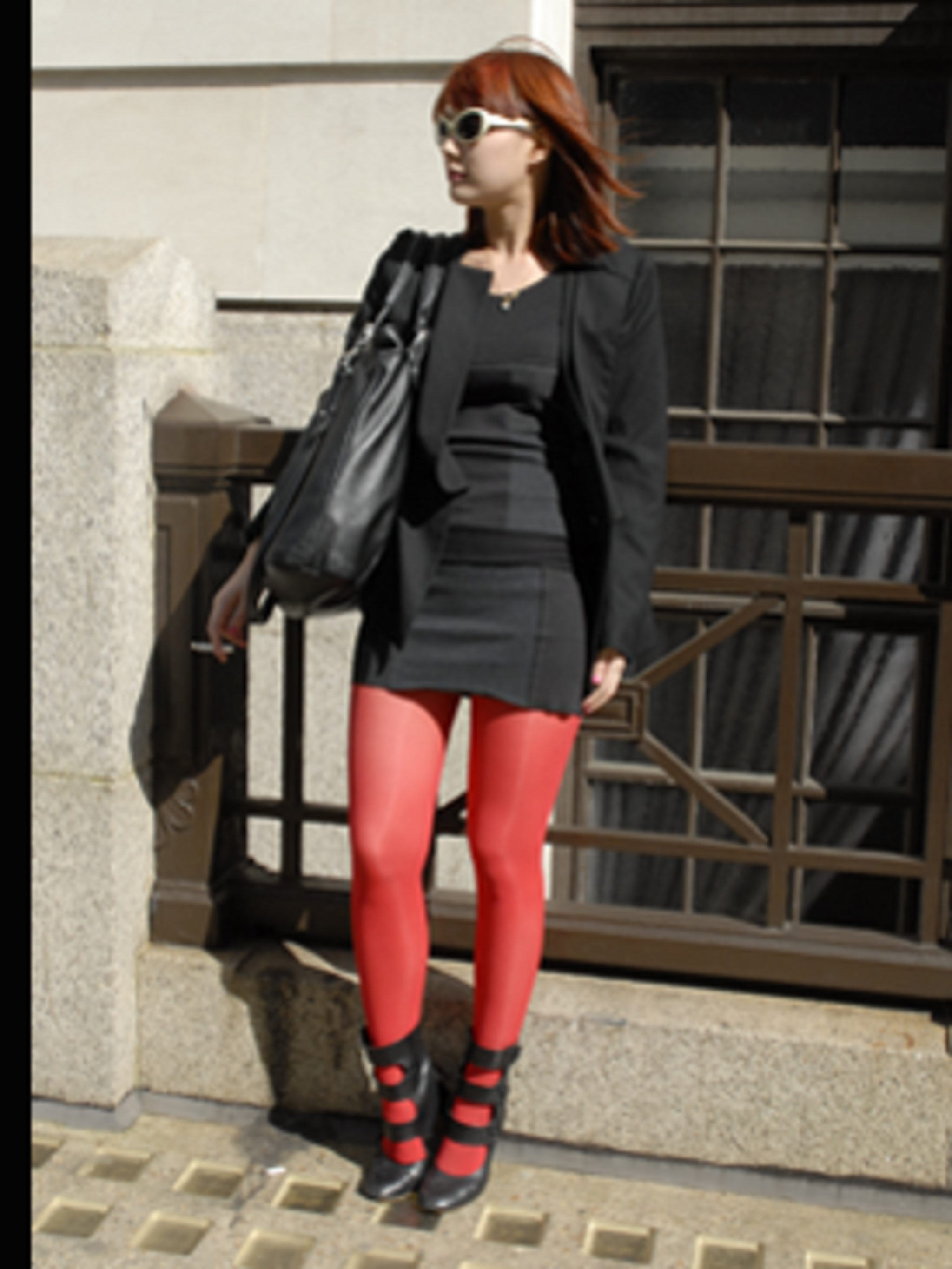 <p>A chic black outfit is given a kooky edge with bright red tights and matching hair. The Eley Kishimoto fetish-esque shoes add sex appeal.</p>