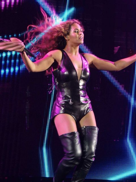 <p>Beyonce wears a black body suit and thigh high boots.</p>
