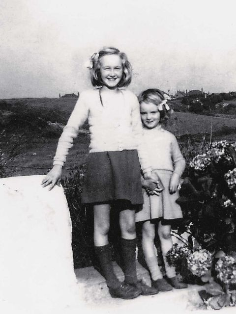 <p>'With my sister, Rosemary, in my mother's knitting, beside the hydrangeas, Tre-Arddur Bay, 1945'</p>
