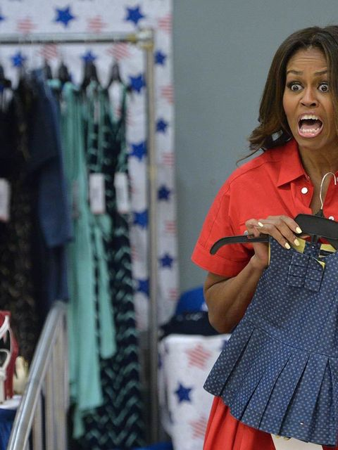 Michelle Obama holds children's clothing as she meets with women expecting babies at the United States and Nato military base in Aviano, Italy, June 2015.