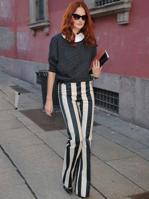 <p>Taylor Tomasi wearing graphic black and white stripe bootcut trousers whilst out during Milan fashion Week.</p>