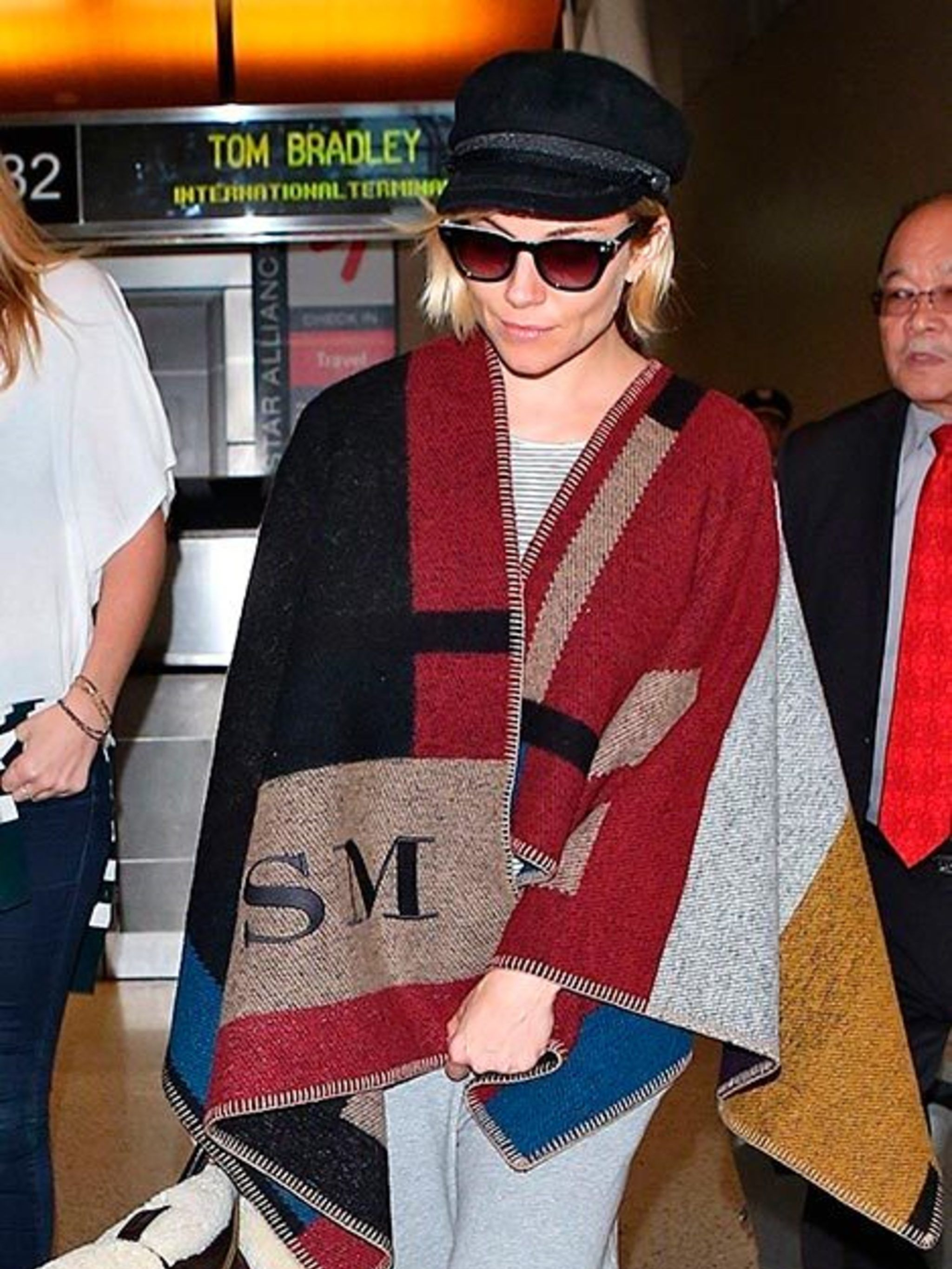Sienna Miller spotted in a Burberry blanket coat at the Los Angeles airport, November 2014.