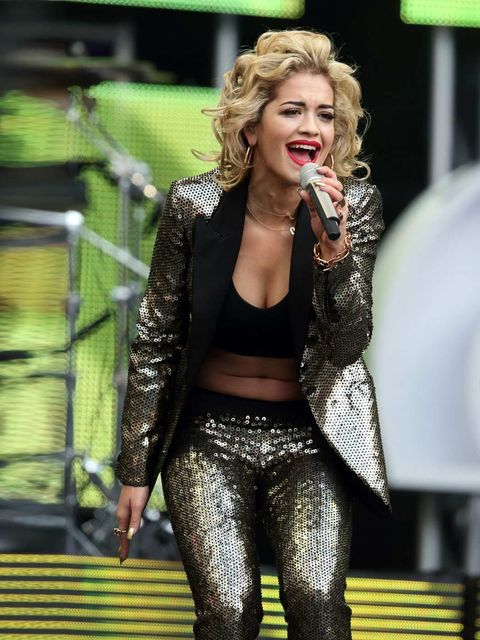 <p>Rita Ora performs in a Gucci one-of-a-kind gold all-over sequined peak lapel one button tuxedo with black suede high heel caged booties.</p>