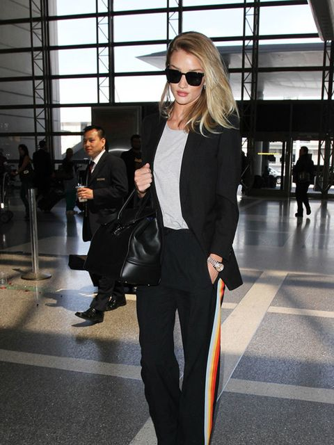 Rosie Huntington-Whiteley teams her Chloe trousers with simple separates and shows us how to do chic airport style whilst jetting into LAX, April 2016.