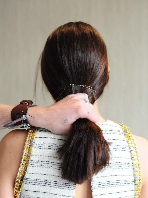 <p>Hold your hair in a ponytail and grip the hair along the top of your hand. Grips at either edge should go inwards to hold the hair in place. </p>