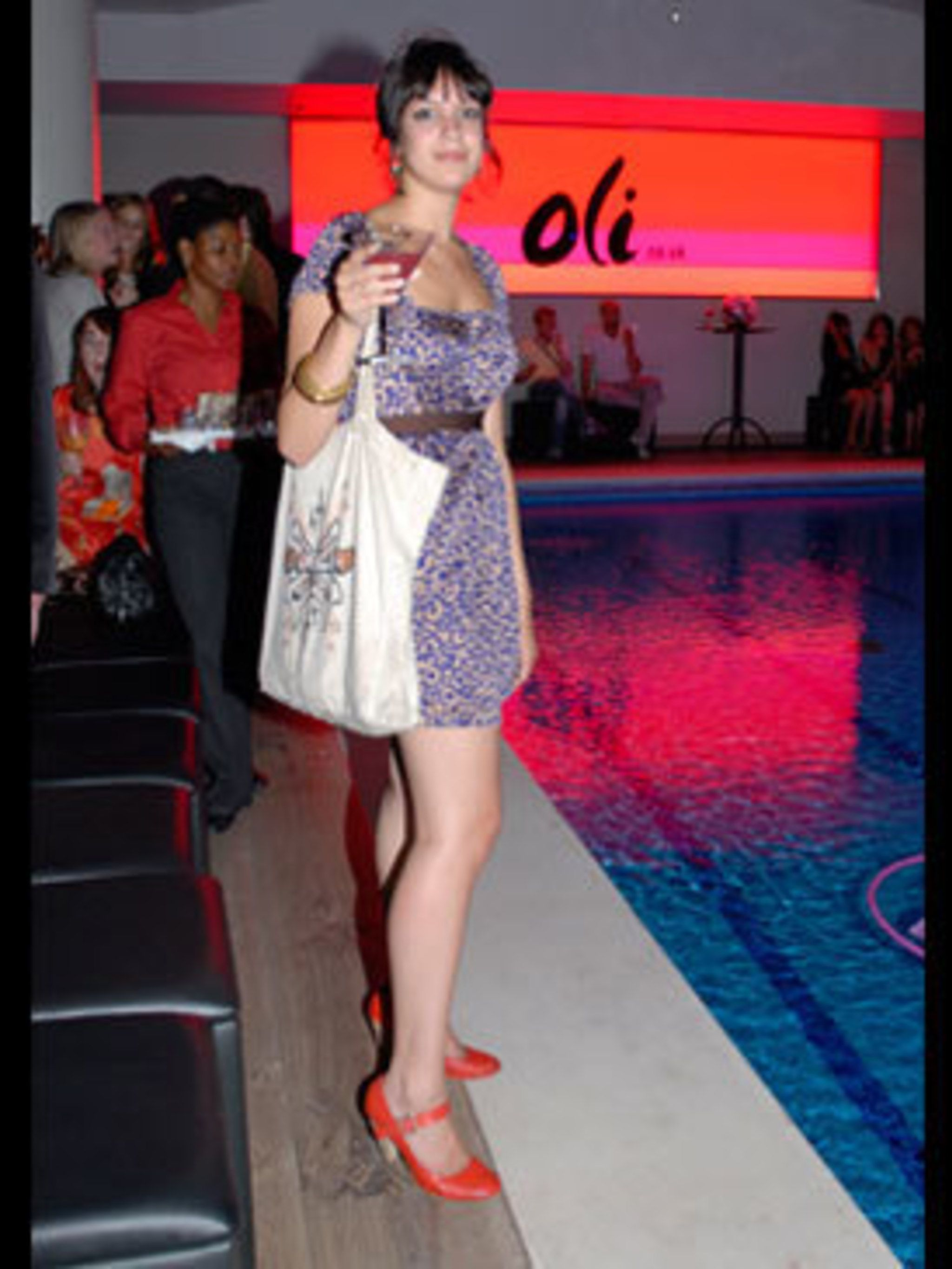 <p>Pairing a purple dress with ruby red shoes appears to be a trend at the launch. Caroline's floral dress has been brought right up-to-date with a skinny tan belt cinching in her waist. Doing her bit for the environment, she has re-used her free eco bag