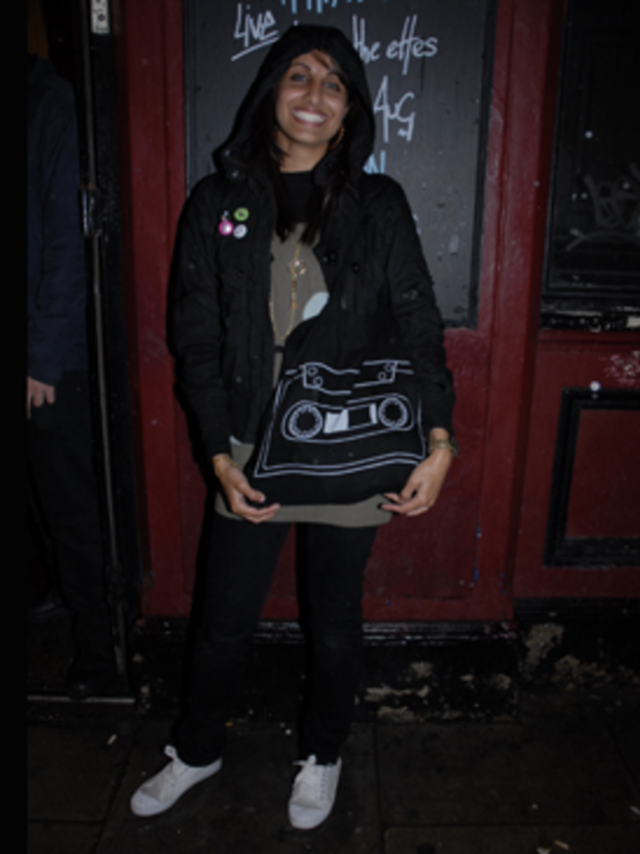 <p>Saima's rocking the indie look with her kids H&amp&#x3B;M black coat adorned with nu-rave bright button badges. Her cassette bag adds an element of fun and the black skinnies and white retro gym shoes finish off her perfect low key 'night down the pub' look