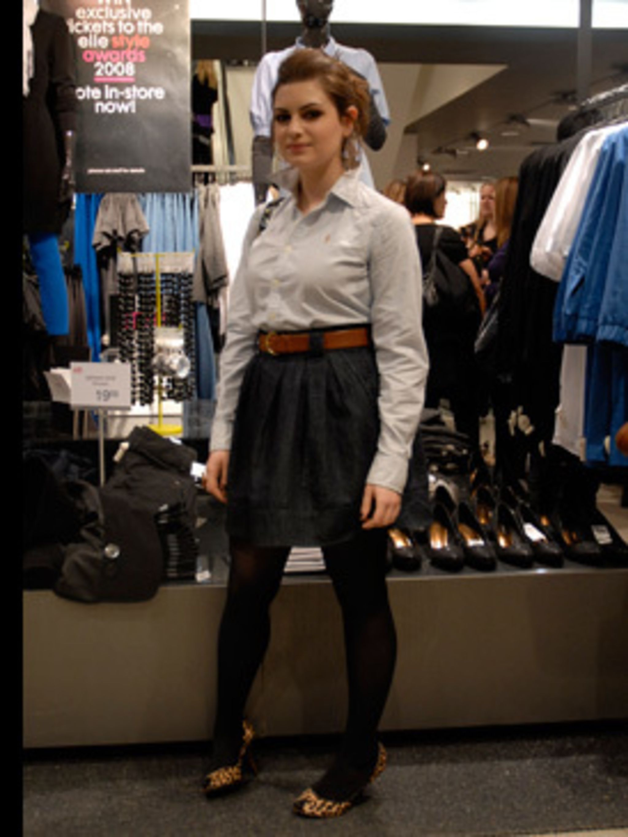 <p>Zarah's signature style is preppy and she has got the look just right with a pale blue shirt, tan belt and high waist navy skirt.</p>