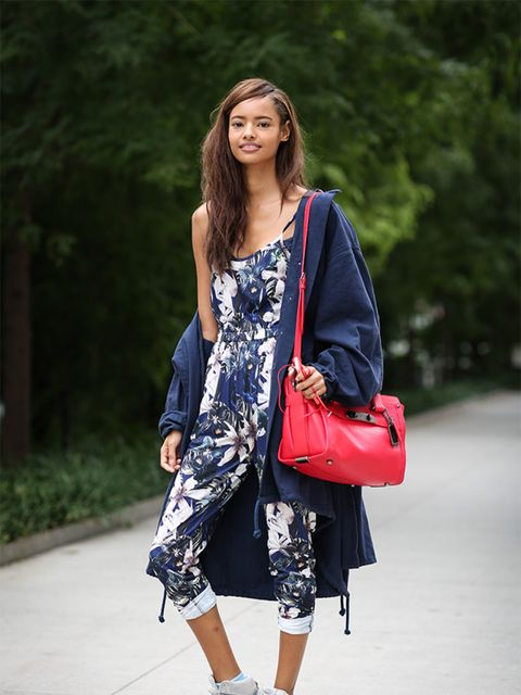 Malaika Firth wears Topshop coat and jumpsuit, Coach bag and Nike trainers.