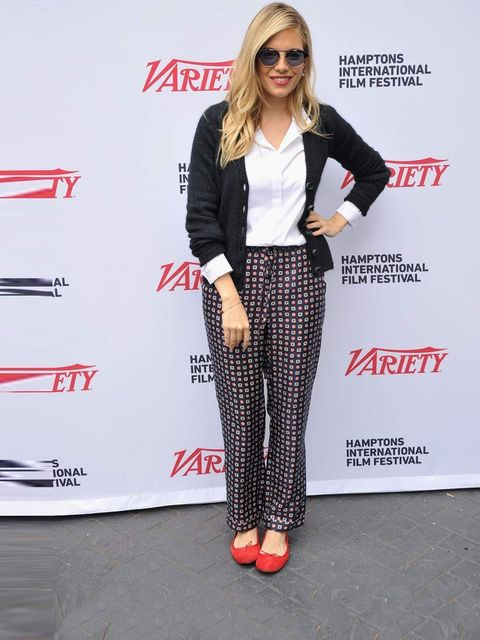 <p>Sienna Miller matches a pair of red Repetto ballerina flats with Sea NY cravat print trousers at the Hamptons Film Festival.</p>