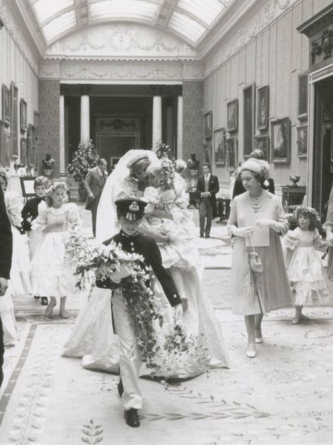 Princess Diana carries five-year-old Clementine Hambro, her youngest bridesmaid, while walking with Queen Elizabeth