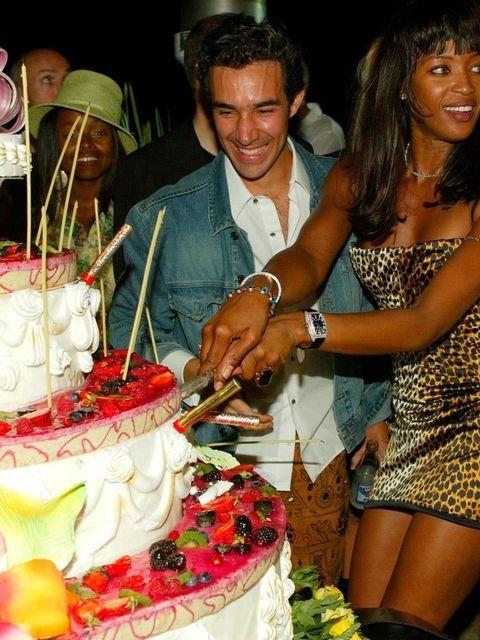 <p>Naomi Campbell cuts her cake.</p>