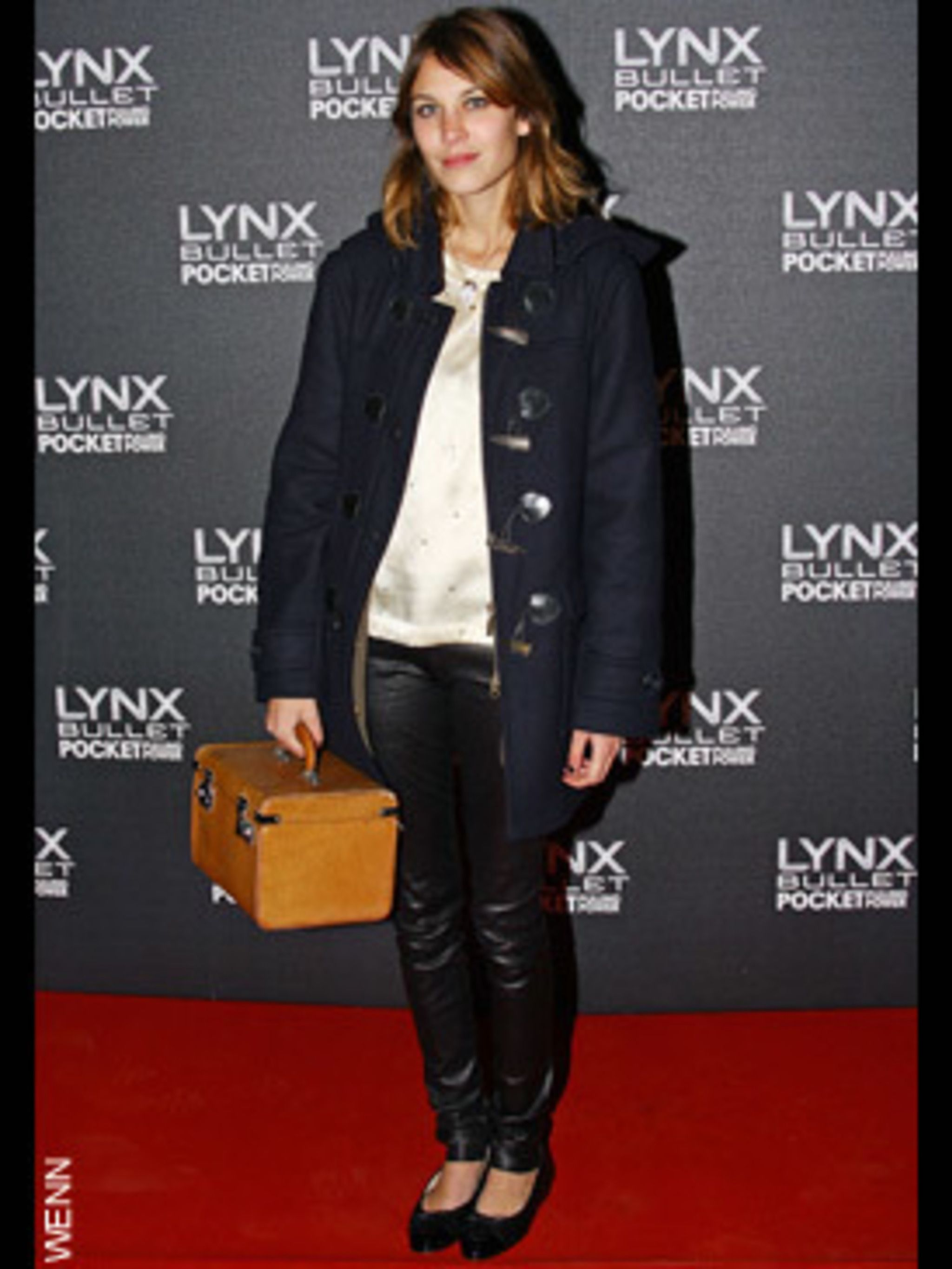 <p>Ever the vintage style queen, Alexa dresses down her glam wet-look leggings with a duffle coat and an over-sized box bag</p>