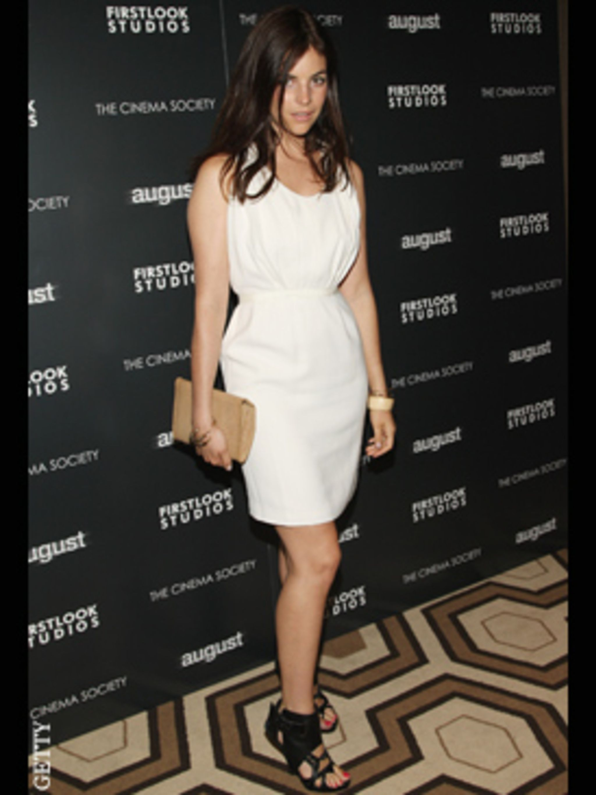 <p>Julia Roitfeld toughens up a pretty white dress with gladiatorial heels.</p>