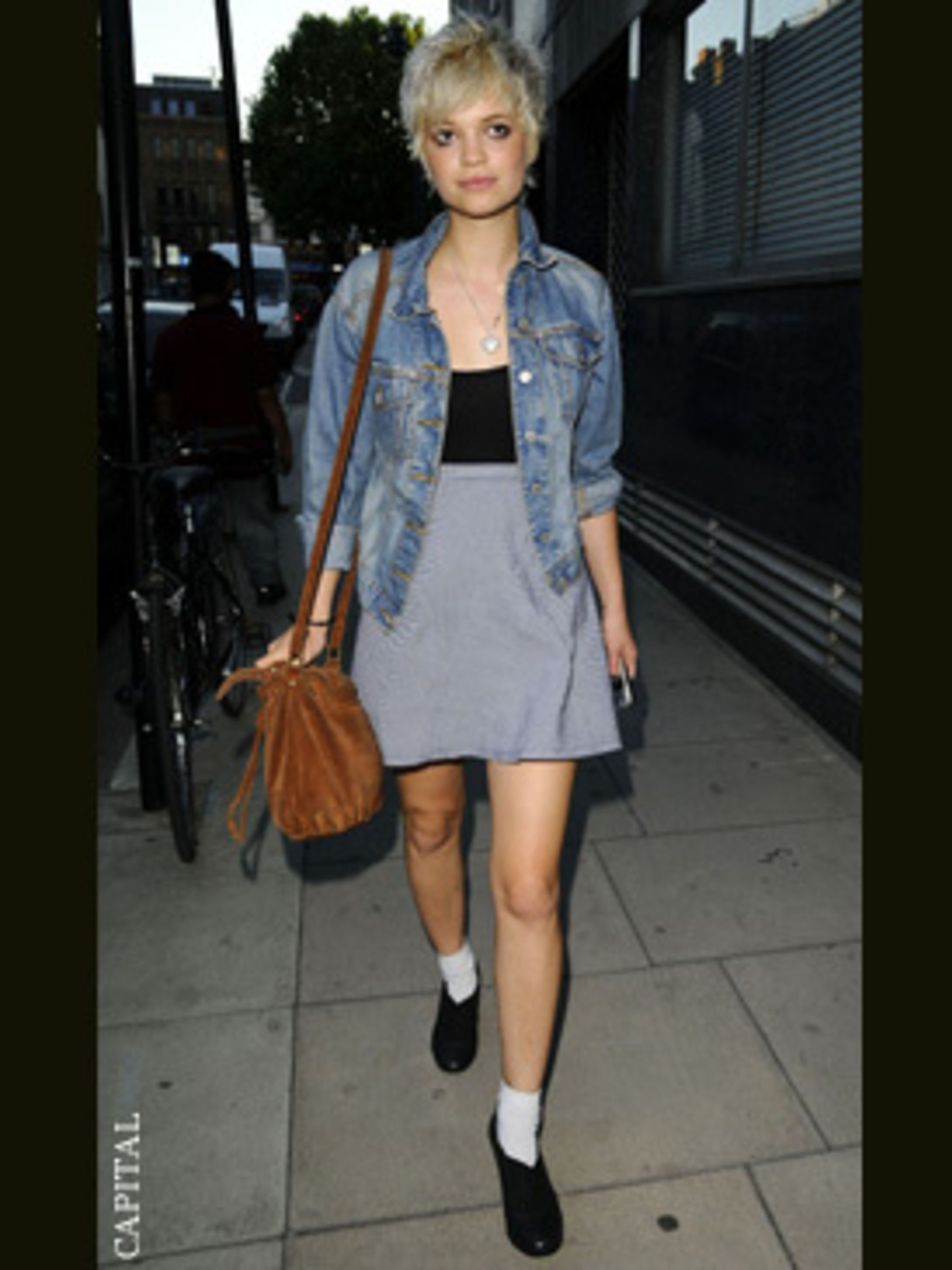 <p>Pixie Geldof works 1980s pale denim and bodycon trend in a vintage jacket, vintage suede bag and a body stocking</p>