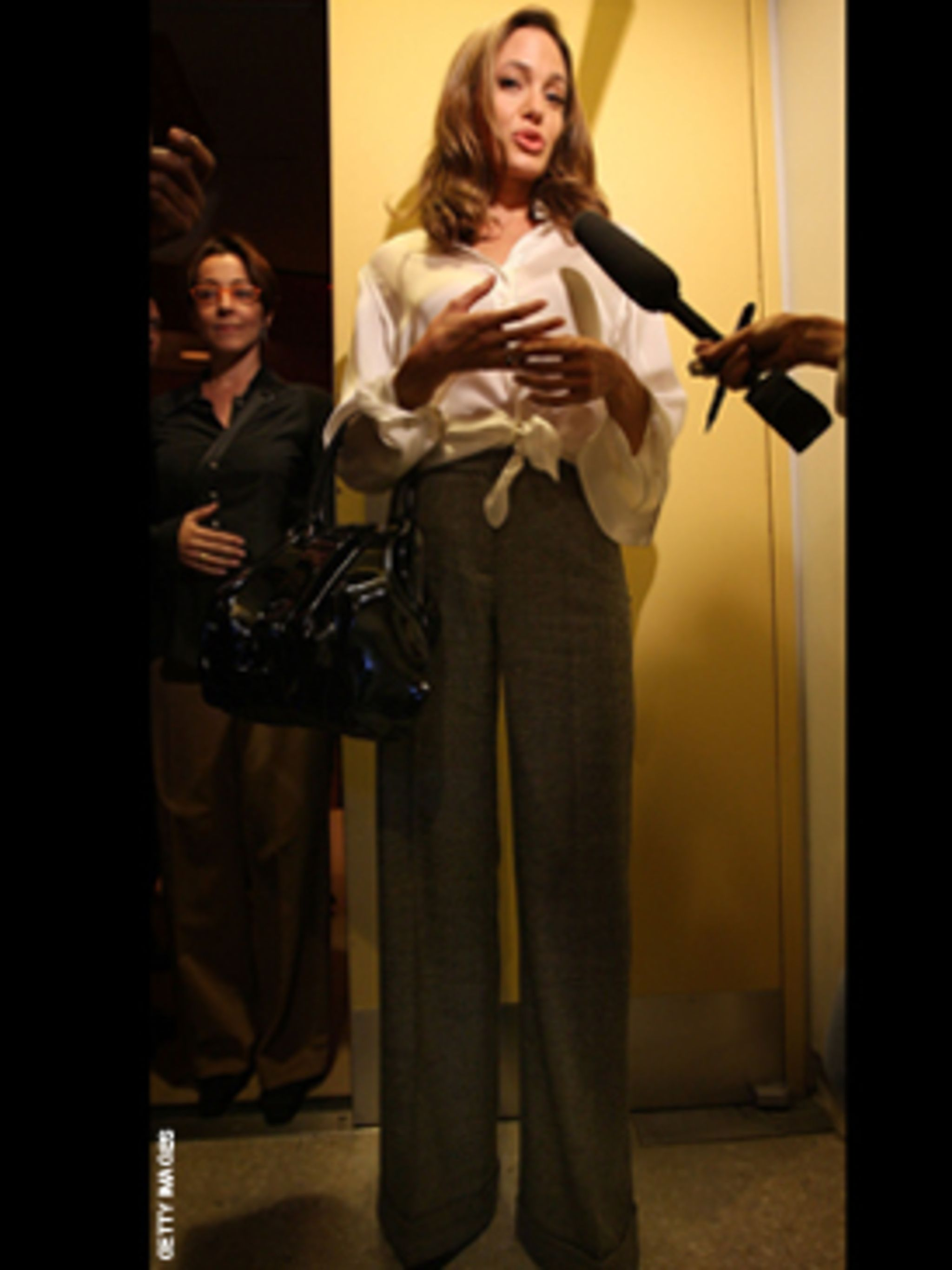 <p>Angelina teams her high waisted tweed trousers with a ladylike blouse - perfect!</p>