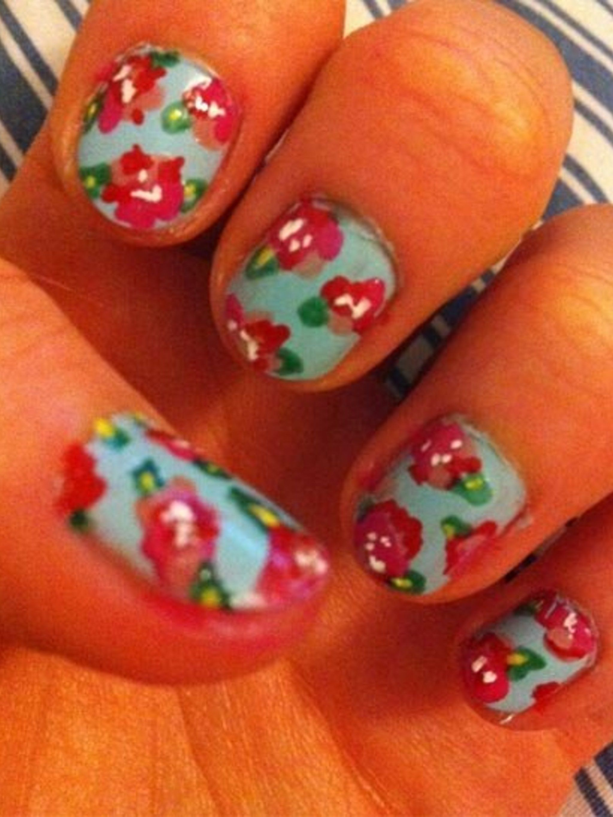 <p>For this Cath Kidston inspired design start off by painting your nails in a pale blue.</p><p>You need three shades of pink varnish for the petals. Place a blob of the darkest shade onto the nail and then apply the two lighter shades with cocktail stick