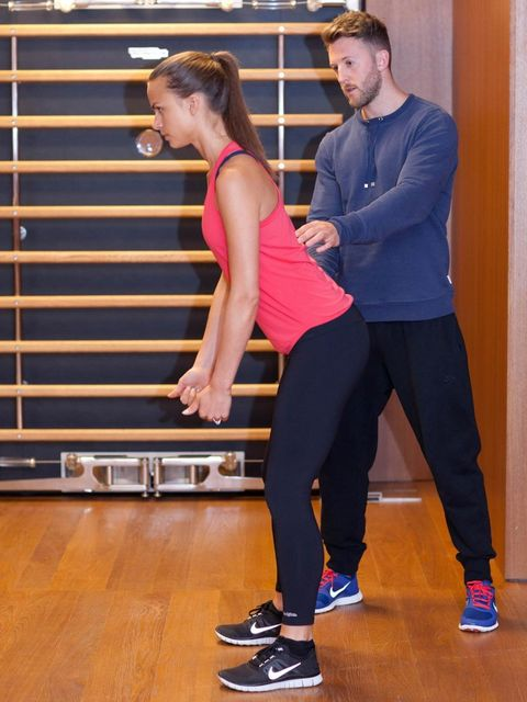 <p>Stand with feet shoulder-width apart, chest up, shoulders back, and spine straight. Bend your knees slightly and sit your hips back slightly, so your bum sticks out. Keep your arms straight and your thumbs up towards the ceiling.</p>