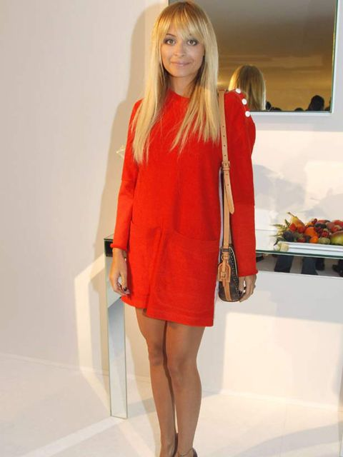 <p>Nicole Richie is wearing a red dress with black shoes and a shoulder bag at the Louis Vuitton show Spring/Summer 2012, October 2011.</p>