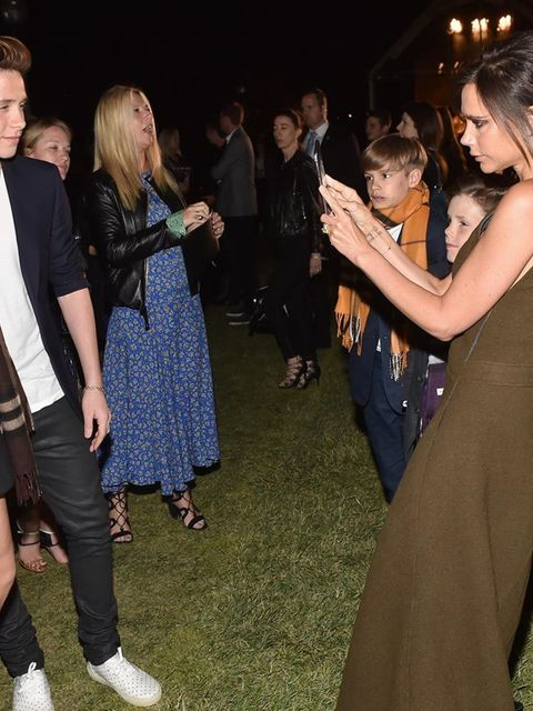 <p>Victoria takes of snap of Brooklyn and Cara Delevingne for Brooklyn's instagram during Burberry's 'London in Los Angeles' event, April 2015</p>