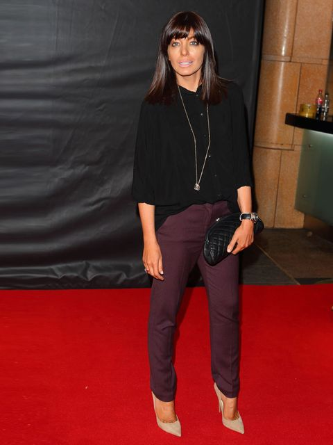 <p>Claudia Winkleman wears purple trousers, black shirt and a black quilted clutch at the Sweeney premier</p>