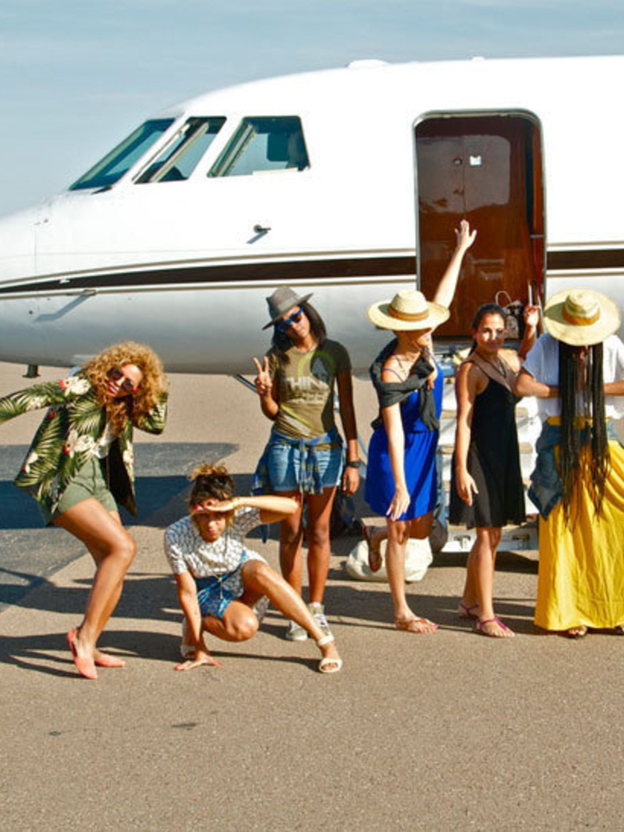<p>Beyonce and her friends posing in front of a private jet</p>