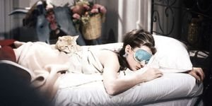 Audrey Hepburn sleeping in bed with a cat