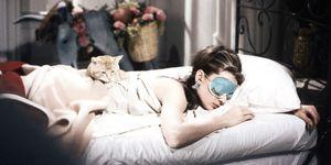 Audrey Hepburn sleeping in bed with a cat