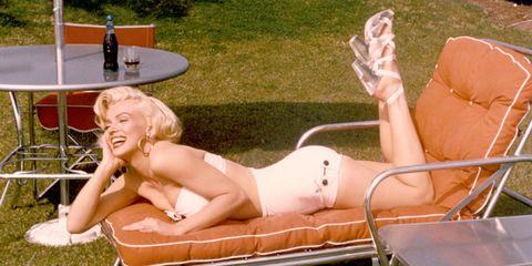 Sun tanning, Blond, Leg, Leisure, Furniture, Bikini, Chaise longue, Long hair, Couch, Thigh,
