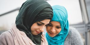 muslim women in headscarves looking at a phone
