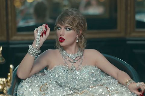<p>While taking the world's most-painful bath to wash the dead off of her, Taylor rocks a super-smudgy cat eye, a loosely curled&nbsp;chignon, and some vinyl red lips to match her dangerously sharp nails.&nbsp;</p>