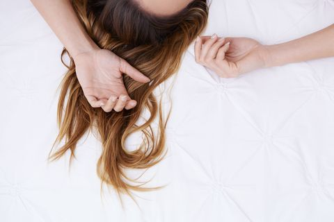 Cropped image of a woman's hair lying sprawled on a bed | ELLE UK