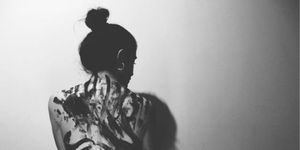 Rear View Of Woman Standing Against Wall, Domestic Abuse | ELLE UK