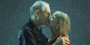 senior couple kissing - old couple in the rain
