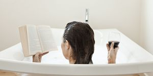woman in bath reading with glass of wine | ELLE UK