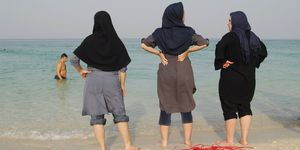 Three women with their trousers rolled up chill out on the shore of Kish Island enjoying lesser restrictions imposed on visitors. Iranian women are not allowed to swim in a bathing suit, their body must be covered at all times while in public | ELLE UK