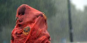 An Indian woman covers her baby under her saree during heavy rain at Rajpath in New Delhi on August 7, 2017 | ELLE UK