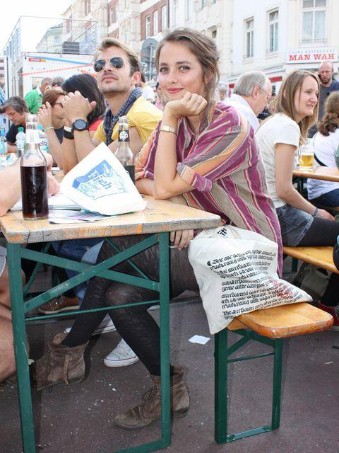 Sitting, Drink, Bottle, Outdoor furniture, Scarf, Outdoor table, Plastic bottle, Handbag,