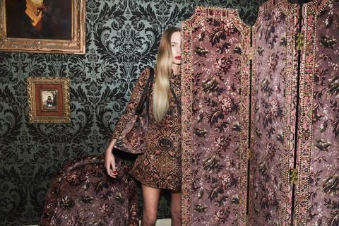 Clothing, Beauty, Fashion, Dress, Brown, Long hair, Tree, Wall, Outerwear, Pattern,